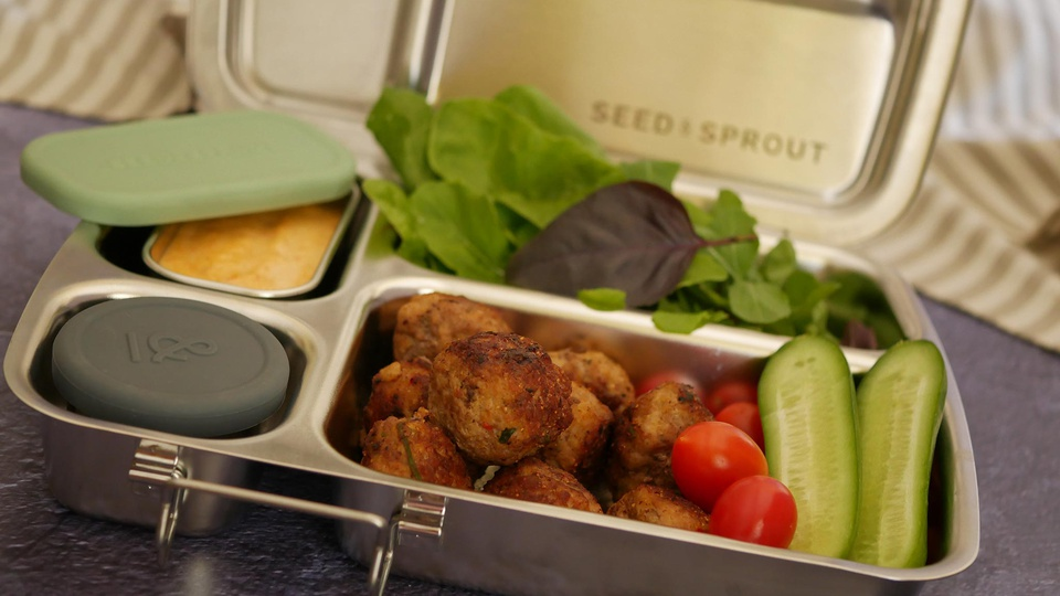 Metallic lunchbox filled with small meatballs salad leaves and crudités
