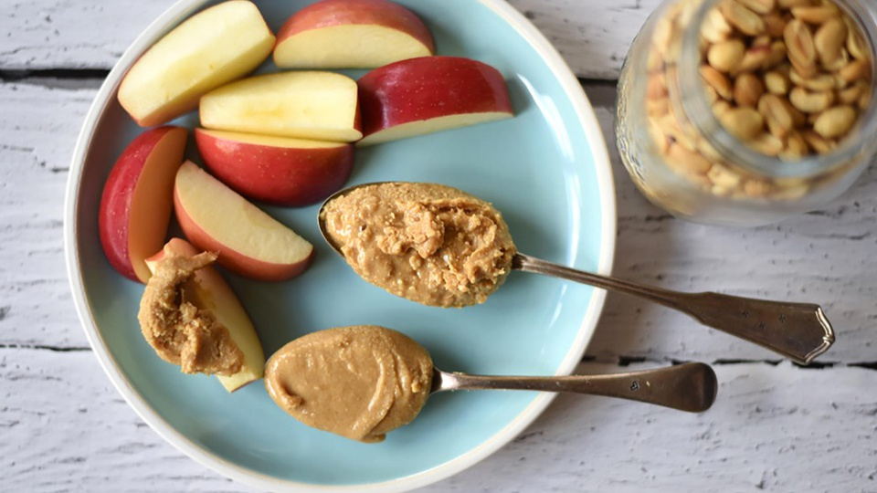 Plate of apple slices with heaped spoonfuls of crunchy or smooth peanut butter