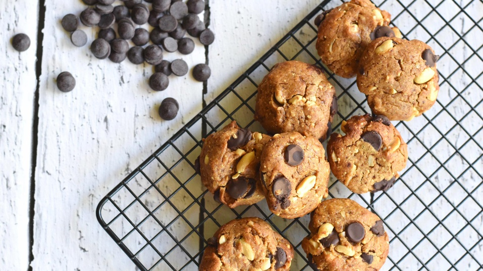 Bite sized peanut butter cookies with chocolate chips rest on wire rack