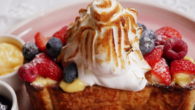 Golden brown brioche french toast topped with soft white and browned meringue with fresh berriesand powdered sugar