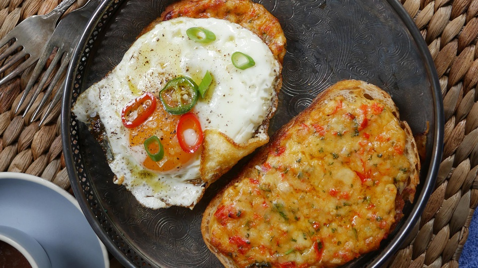 Two slices of cheesy tomato bread with herbs one topped with sunny side up egg and chilli