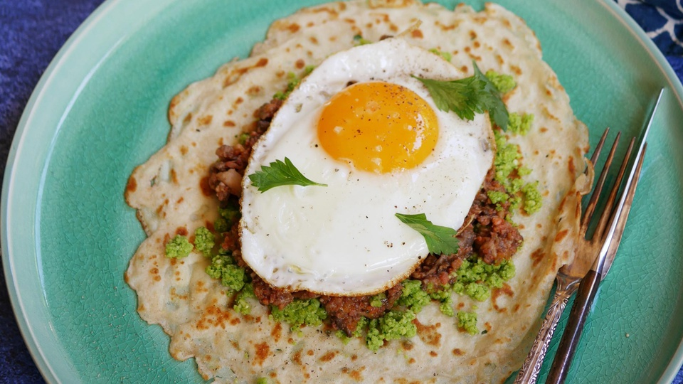 Thin savory crepe with golden brown patches topped with bright green herb mix and deep brown chorizo and frieg egg