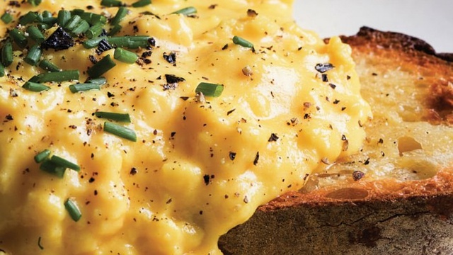 Close up of butter yellow loose scrambled eggs with pepper chives and golden toast