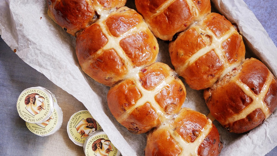 A tray of glazed white chocolate and cranberry hot cross buns served with butter