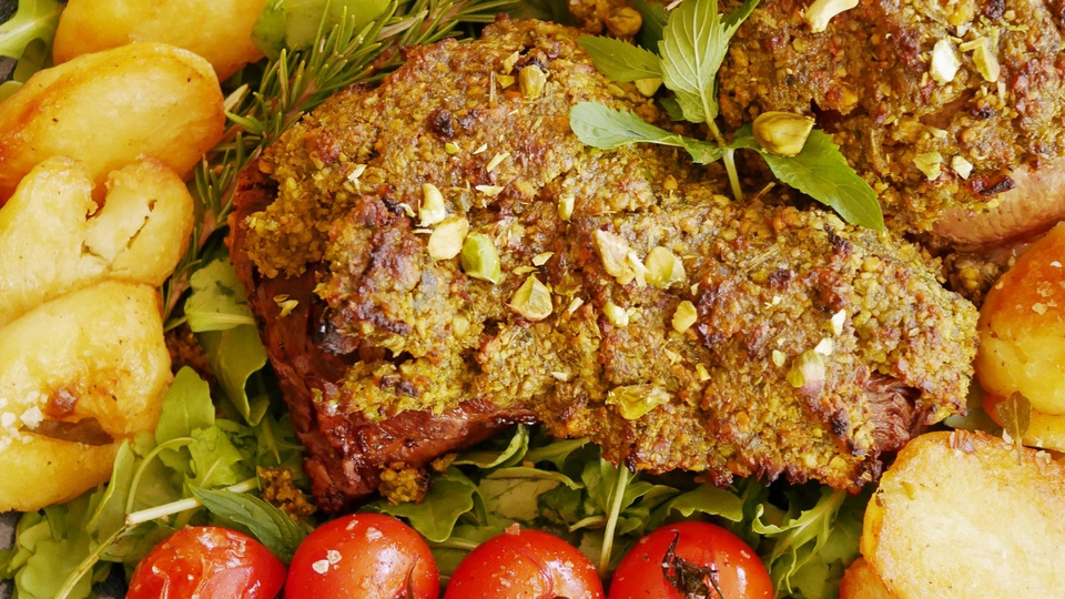 Thick lamb of leg with pesto crust garnished with herbs whole cherry tomatoes and potatoes