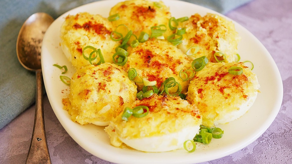 Breaded Polish stuffed eggs with golden crumbs seasoned with red paprika