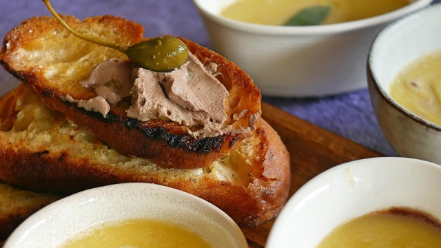 Charred baguette smeared with chicken liver pate mousse topped with an olive