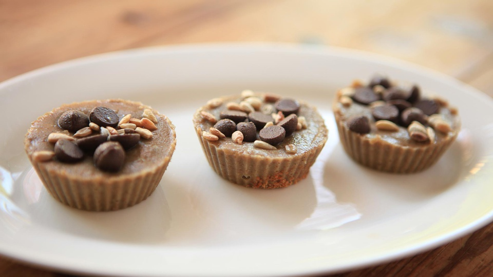 Three sunbutter hemp protien cups with dark chocolate drops and pine nuts