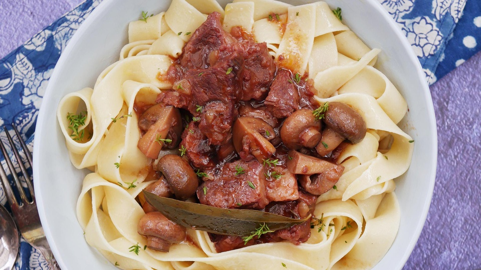 Chunks of tender beef in rich burgundy sauce with onions mushroom and fresh thyme on a bed of thick pasta