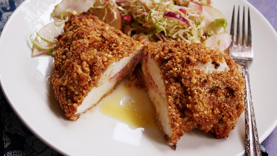 Juicy crumbed chicken breast bisected reveals ham and cheese inside served with slaw salad