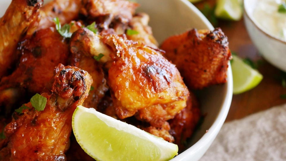 Bowl of crispy, ruby chicken wings with wedges of fresh lime and corriander