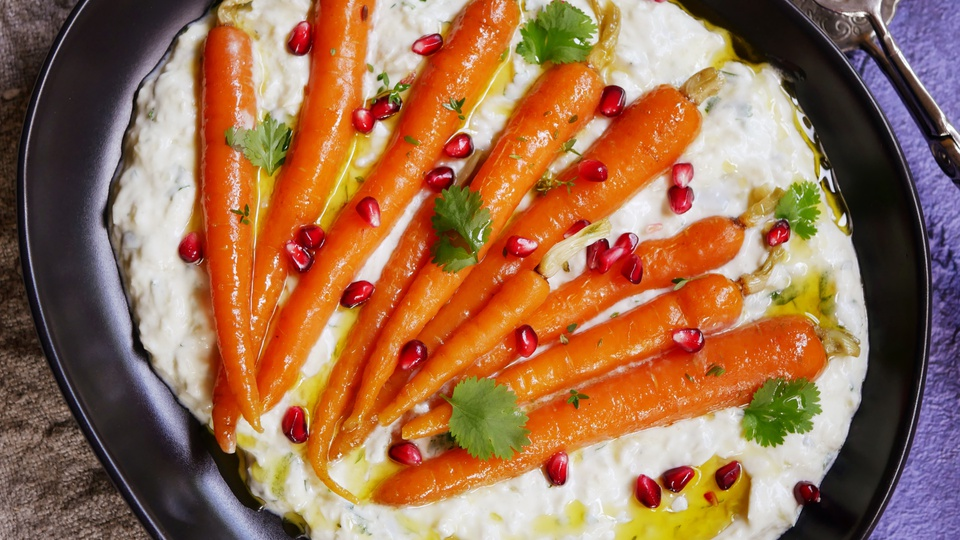 Baby carrots on a bed of spiced yogurt with pomegranate seeds drizzled with oil and fresh parsley
