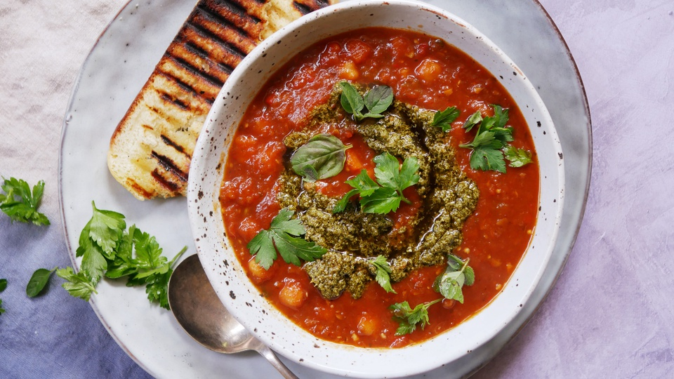 Bowl of thick chickpea minestrone soup served with charred bread and fresh basil