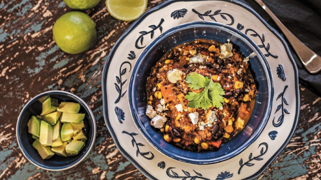 Black bean chilli with quinoa feta sweetcorn and fresh parsley served with avocado