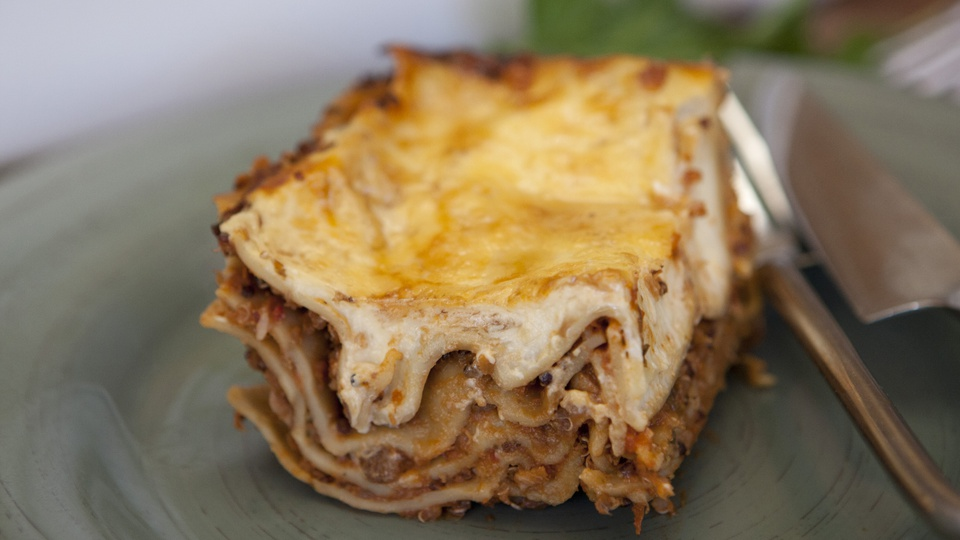 Cross section of lasagne shows sheets of pasta quinoa mushrooms and melted cheese
