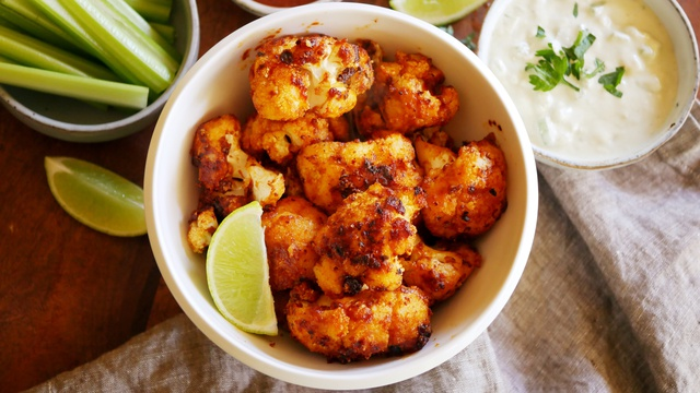 Bowl of charred red and orange buffalo cauliflower florets with lime and dip