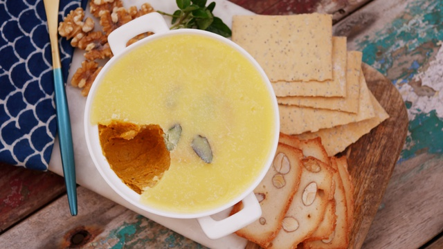 Ramekin with creamy pumpkin and walnut pate with a cap of butter and crackers