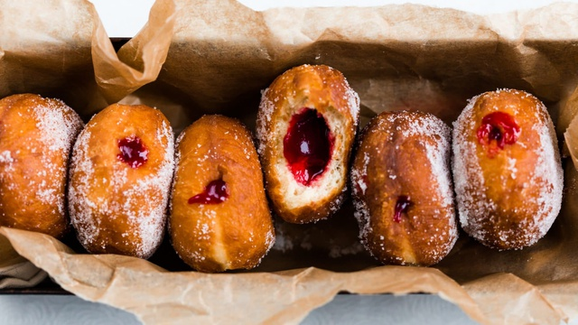 Tin of sugar coated golden brown donuts leaking ruby jam