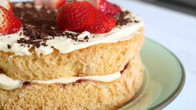 Airy and soft sponge cake sandwiches whipped cream and jam topped with fresh strawberries and grated chocolate