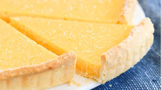 Sweet pastry tart with butter yellow lemon custard filling dusted with sugar