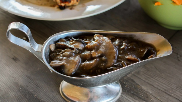 Earthy brown mushroom gravy with slices of sauteed mushrooms in a gravy boat