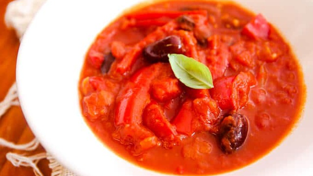 Bright red puttanesca sauce with chunks of pepper olives and onion with fresh basil