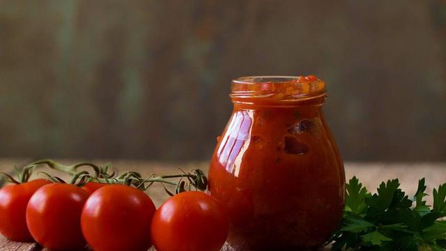 Bulbous glass jar of red keto pizza marinara sauce with fresh vine tomatoes