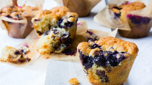 Golden bluberry muffins with indigo marbling encased in brown paper