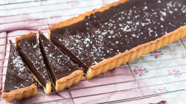 A large rectangular rich chocolate tart with salt flakes cut into segments