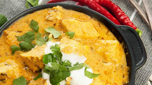 Pot of golden curry with chunks of chicken yogurt and fresh coriander
