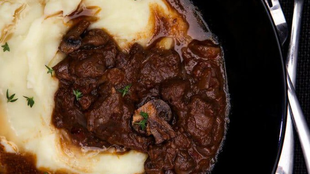 Deep black pot of reddish brown beef bourguignon with creamy mashed potatoes and fresh thyme