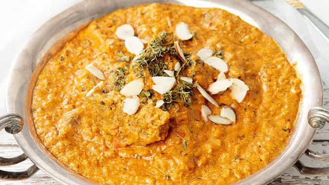 Ornate metal dish with orange beef curry with sliced almonds fresh herbs served family style