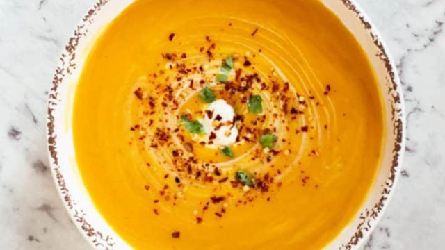 Thick and creamy orange pumpkin soup with chili flakes served with fresh herbs and a blob of coconut cream