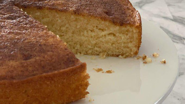 A brown and cinnamon specled tea cake with a perfect slice revealing yellow sponge