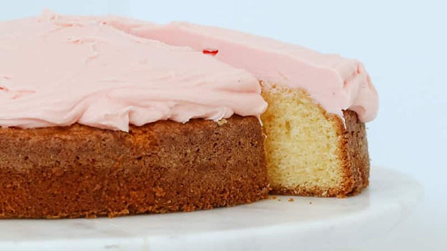 Crumbly vanilla cake with perfect brown crust topped with pink buttercream icing