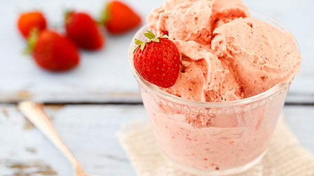 Glass full of pink strawberry ice cream topped with fresh strawberry