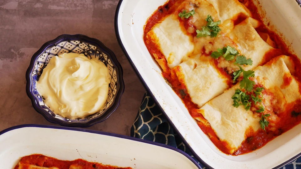 Baking dish full of tomato sauce holds three flour tortilla enchilads topped with melted cheese