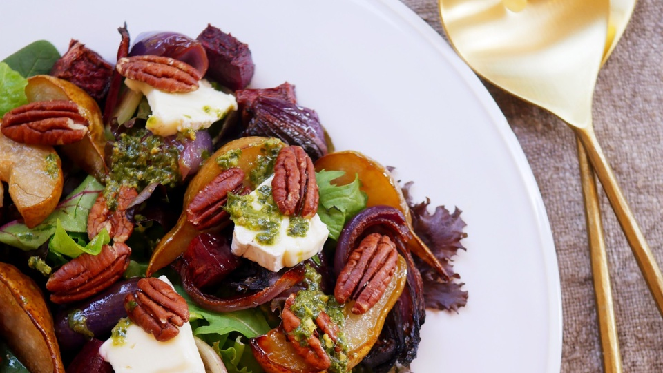 Harvest colors of beet, pecan, pear and mixed leaves salad with pesto drizzle and chunks of creamy brie