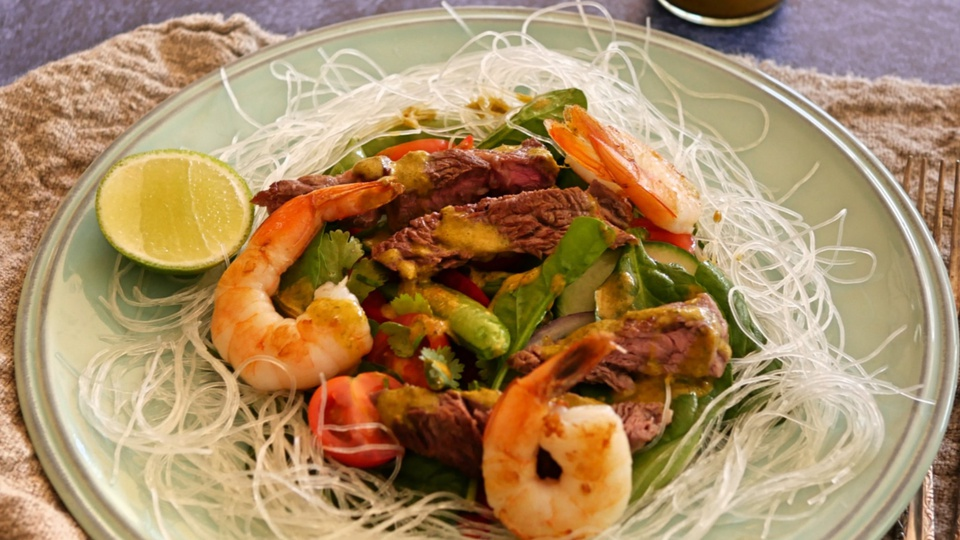 Strips of beef with prawns on top leafy salad on a bed of vermicelli noodles with thai dressing