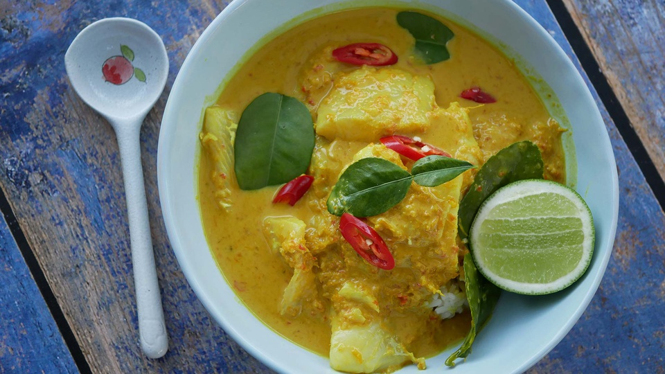 Golden yellow curry in a white bowl with rice red chilli and lime wedge garnish
