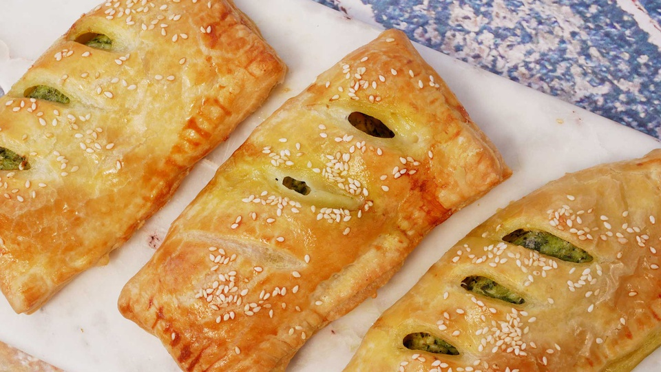 Slits in crispy golden brown pastries reveal green pesto and chicken filling