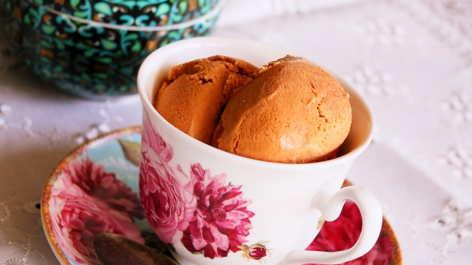 Terracotta colored scoops of Thai Tea Ice Cream served in a teacup and saucer
