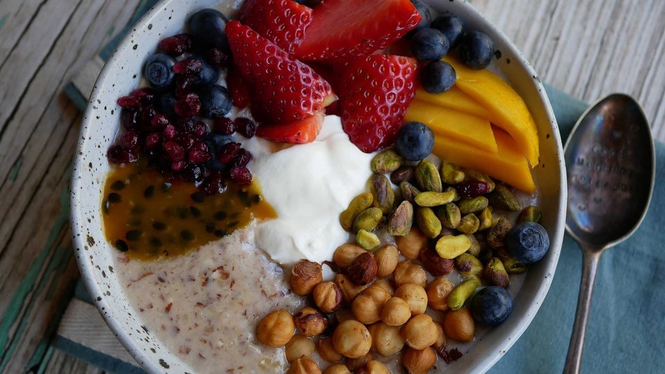 Bowl of almond oatmeal filled with fresh rainbow colored fruits and nuts