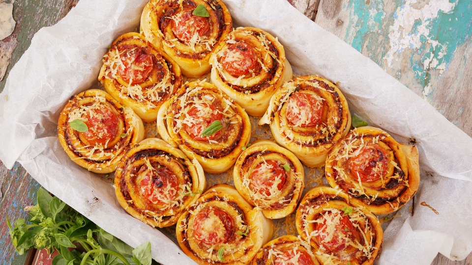 Savory scrolls of pastry ooze marinara topped with grated parmesan and basil