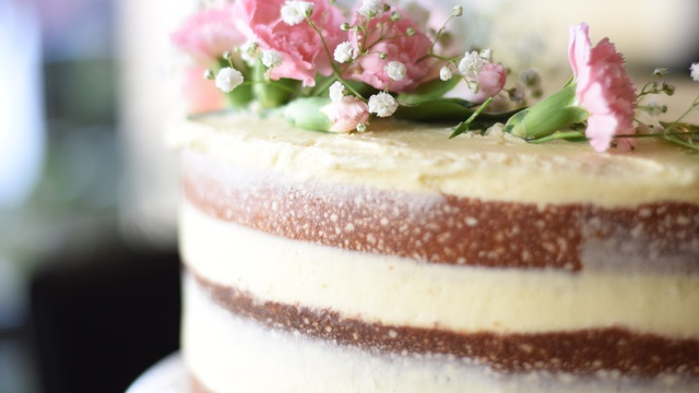 Sandwiched layers of white icing on top of brown butter cake topped with flowers