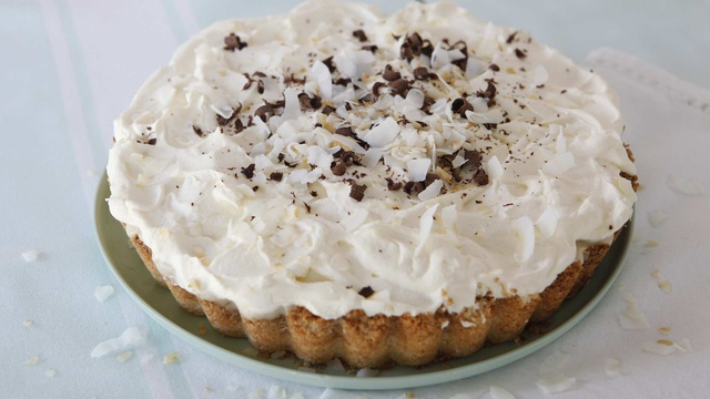 Coconut pie served with whipped cream with chocolate and coconut shavings