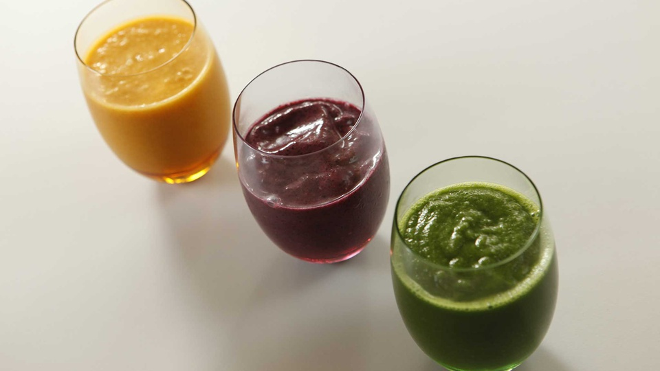 Three thick healthy smoothies of orange green and red