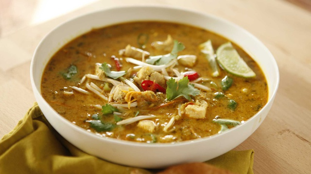 Bowl of appetizing curried coconut chicken soup served with lime parsley and bean sprouts