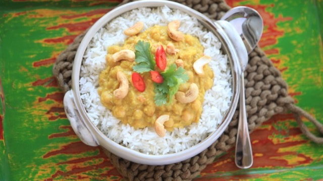 Golden chickpea curry is served on fluffy white rice, topped with cashews and fresh red chilli