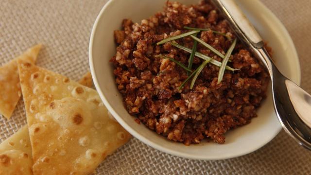White bowl of nutty Tuscan almond pesto with fresh rosemary